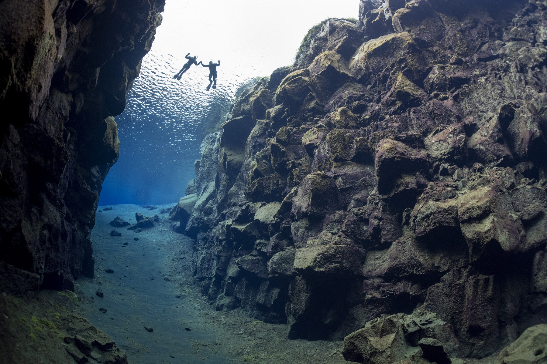 snorkelers-hold-hands-in-silfra-iceland-divers-view